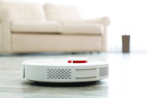 Modern robotic vacuum cleaner on floor in living room. Space for